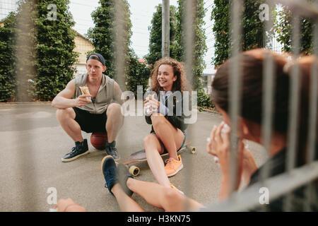 Gruppo di amici seduti all'aperto pallacanestro mangiare e divertirsi. Gli adolescenti rilassante pallacanestro. Foto Stock