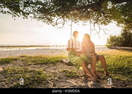 Due donne seduto sulla spiaggia di rotazione di albero al tramonto, Gili Trawangan, Lombok, Indonesia Foto Stock