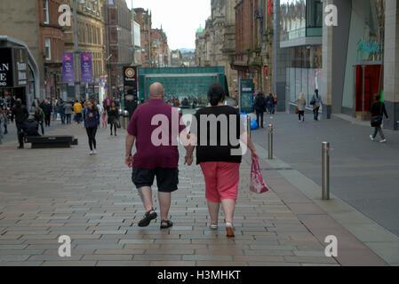 Glasgow scene di strada sovrappeso giovane tenendo le mani sul Buchanan Street Foto Stock