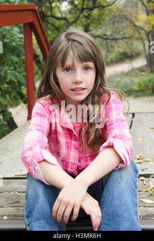 Poco ragazza seduta sulle scale di legno di rosa colorato plaid shirt e in posa per la fotocamera Foto Stock