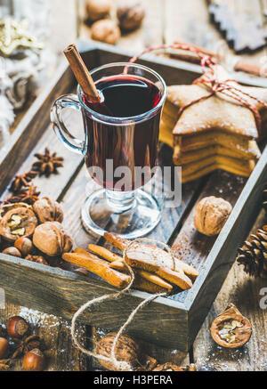 Bicchiere di vin brulé con gingerbread cookies, noci, spezie Foto Stock