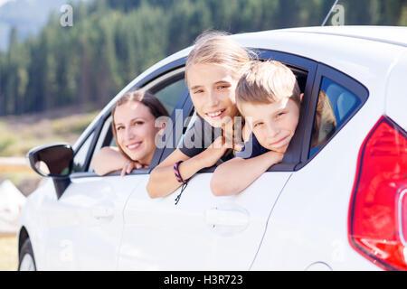 Felice giovane donna e bambini seduti in auto e guardare fuori da Windows. Viaggio di famiglia immagine di sfondo Foto Stock