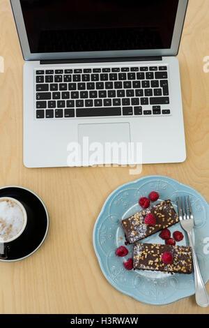 Deliziose torte, una tazza di caffè e il computer portatile sul tavolo Foto Stock