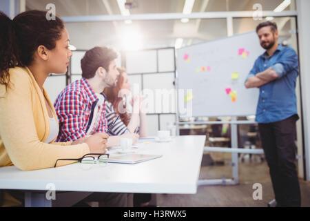 Executive in piedi di fronte ai colleghi in una sala riunioni presso il creative office Foto Stock