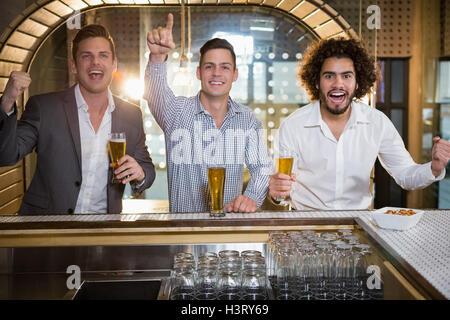 Amici alzando il pugno pur avendo la birra al bancone bar Foto Stock