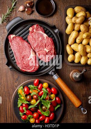 Materie bistecca in padella per grigliare, patate, spezie e pomodori, vista dall'alto, sul tavolo di legno Foto Stock
