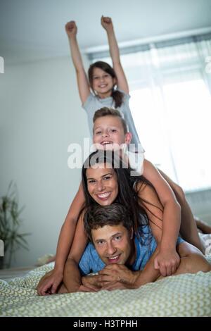La famiglia felice avendo divertimento in camera da letto Foto Stock