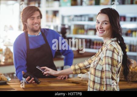 La donna il pagamento fattura tramite lo smartphone utilizzando la tecnologia NFC Foto Stock