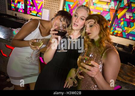 Tre amici di sesso femminile avente un bicchiere di champagne e vino