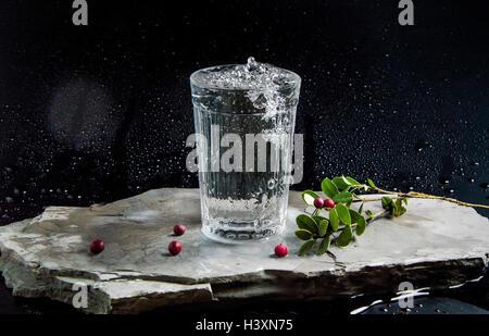 L'acqua viene versata nel bicchiere su sfondo scuro Foto Stock