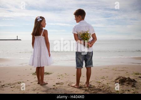 Ragazzo holding fiori alle sue spalle, in piedi accanto alla ragazza sulla spiaggia