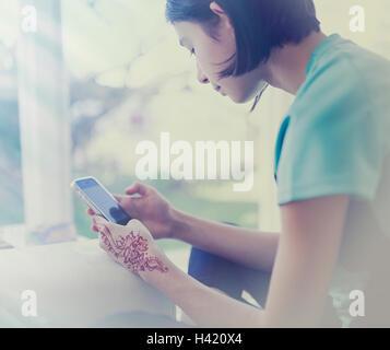 Razza mista ragazza sms sul cellulare vicino a finestra Foto Stock
