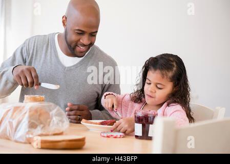 Padre e figlia rendendo panini Foto Stock