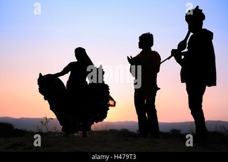 Tramonto, silhouette di donna danza una danza tradizionale con due musicisti, Pushkar, Rajasthan, India Foto Stock
