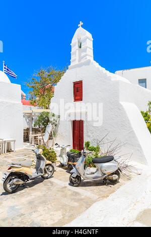 La città di Mykonos, Grecia - 16 Maggio 2016: due scooter parcheggiato di fronte a una tipica chiesa bianca con Foto Stock