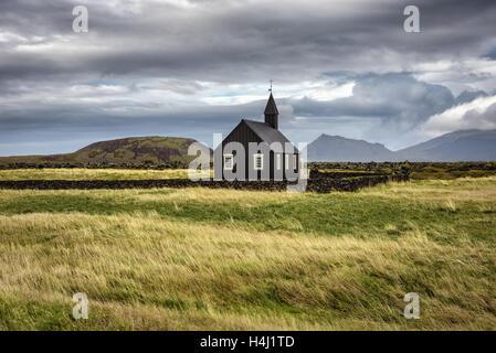 Scenario di legno nero chiesa di Budir in Islanda con il pascolo e le montagne sullo sfondo Foto Stock