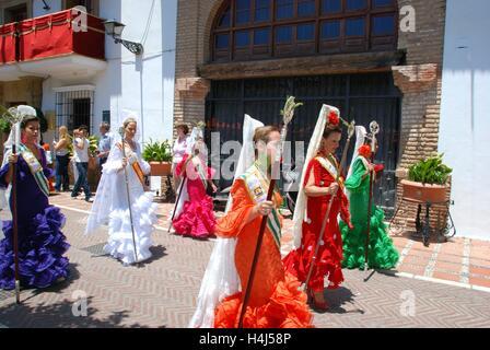 Lo spagnolo le donne in abiti tradizionali a piedi attraverso la strada durante la Romeria San Bernabe, Marbella, Spagna. Foto Stock