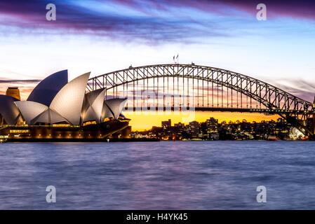 Sydney Opera House e il Sydney Harbour Bridge durante un glorioso tramonto Foto Stock