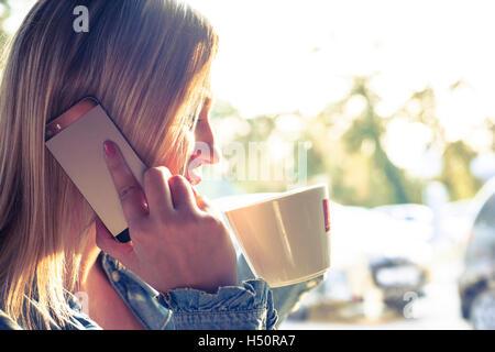 Giovane donna a bere caffè e parlando al telefono cellulare