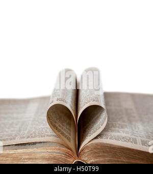 Una vecchia Bibbia aperta con la deliberata concentrarsi sui bordi del a forma di cuore le pagine ripiegate e copia di spazio. Profondità di campo.