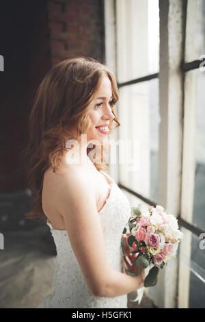 Elegante bellissimo matrimonio sposa in posa vicino al grande arco della finestra