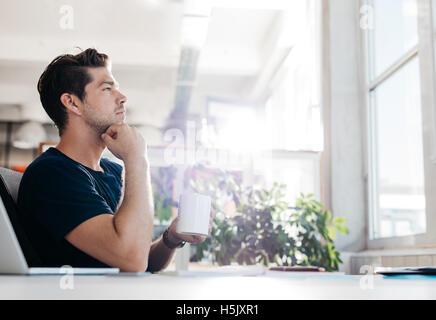 Vista laterale shot del giovane imprenditore con caffè in mano seduto alla sua scrivania. Uomo seduto in ufficio Foto Stock