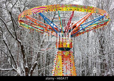 Giostra colorata in winter park contro alberi coperti di neve Foto Stock