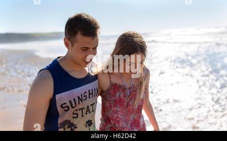 Felice coppia giovane in amore camminando lungo la spiaggia Foto Stock