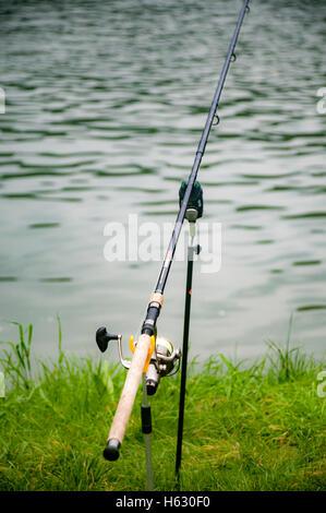 Esca ed asta di pesca sulle rive di un fiume Foto Stock