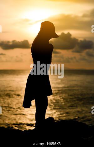 Donna in piedi indossare un cappello con silhouette al tramonto Foto Stock