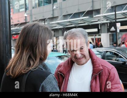 Senior adulto visto a parlare con una giovane donna al di fuori di un negozio al dettaglio nel centro della citta'. Foto Stock