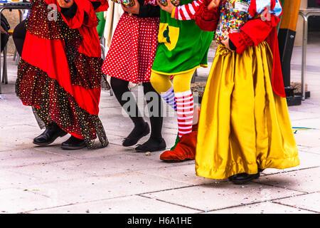 Stagione di carnevale: bambini a camminare insieme sulla strada vestito in variopinti costumi di carnevale Foto Stock