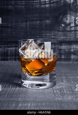 Bicchiere di whiskey con cubetti di ghiaccio sul blu sullo sfondo di legno Foto Stock