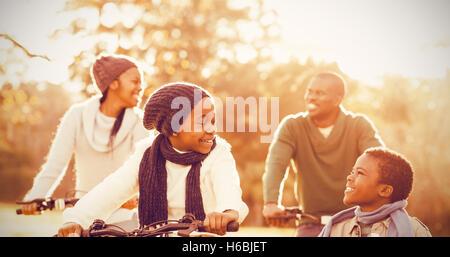 Giovane famiglia sorridente facendo un giro in bici Foto Stock