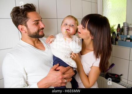 La famiglia felice e salute. Madre di spazzolatura dei denti il loro bambino Foto Stock
