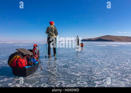 Una donna e un uomo con una mazza e trekking pole è sull'azzurro ghiaccio del Baikal Foto Stock