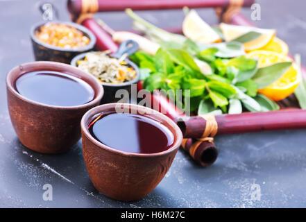 Tè freschi in tazze e su un tavolo Foto Stock