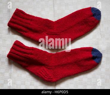 Coppia di calda lana colorata Calze a maglia su un sfondo di lino Foto Stock