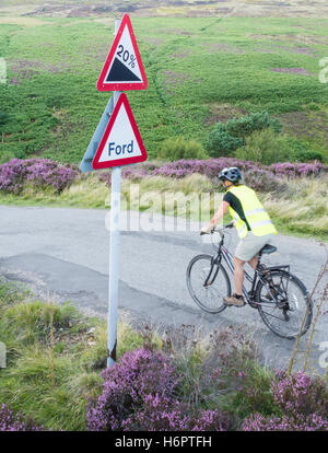 Femmina ciclista su strada di campagna a Westerdale, North York Moors National Park, North Yorkshire, Inghilterra. Foto Stock