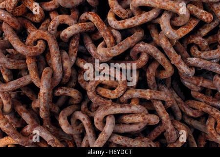 Vecchio arrugginito le catene di ferro come sfondo di una pila di decadimento ossidato maglie metalliche come un simbolo astratto di invecchiamento industriale o corrosione. Foto Stock