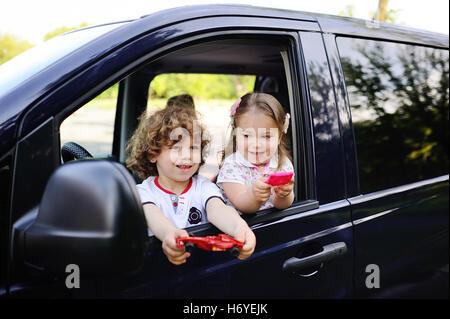 I bambini guardano fuori dal finestrino di un'automobile Foto Stock