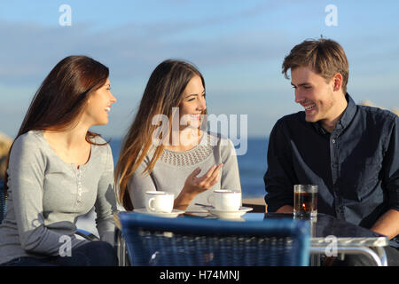 Gli amici di parlare in un ristorante sulla spiaggia Foto Stock