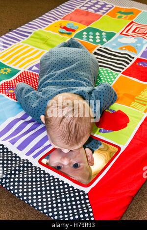 Baby boy giocando su un tappetino di gioco Foto Stock