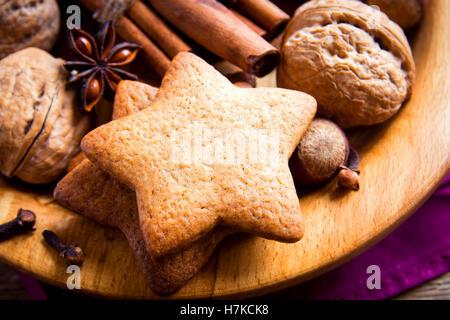 Natale rustico gingerbread cookie, i dadi e le spezie di Natale su piatto di legno vicino fino Foto Stock
