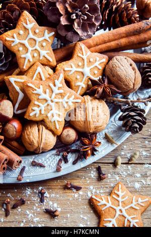 Decorazioni di Natale con fatti in casa gingerbread cookies stelle, coni, i dadi e le spezie di Natale su rustico Foto Stock