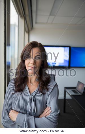 Ritratto fiducioso imprenditrice con le braccia incrociate Foto Stock