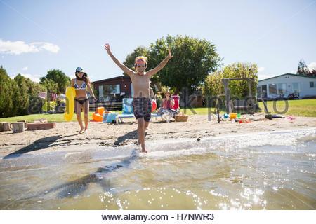 Fratello e Sorella in esecuzione nella soleggiata estate lago Foto Stock