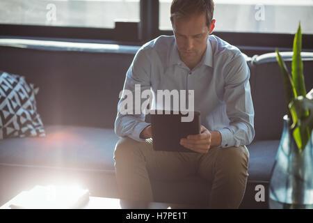 Imprenditore con tavoletta digitale in ufficio Foto Stock