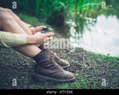 Una giovane donna è seduta da uno stagno nella foresta e sta avendo una tazza di tè Foto Stock