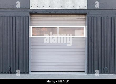 Il cancello chiuso in metallo grigio parete magazzino, sfondo piatto texture foto Foto Stock